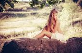 Beautiful nude woman lies on stones against nature background