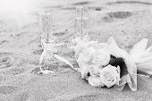 Wedding glasses on sand with a bouquet