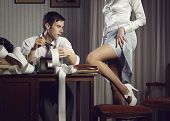 picture of office romance  - Young sexy woman shows a leg for business man at desk - JPG