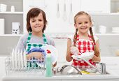 Happy kids helping in the kitchen doing the dishes