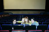 Four young friends sit on seats in cinema theater and turn around back.
