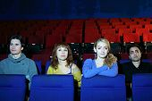 Four young friends watch movie in cinema theater. Focus on girls.