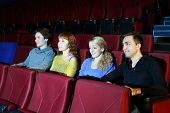 Four young people watch movie in movie theater. Focus on girls.