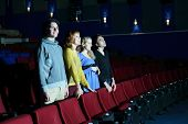 Four happy friends stand and look at screen in cinema theater. Focus on left pair.