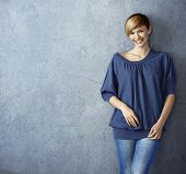 Attractive young woman in blue jeans leaning against wall, smiling