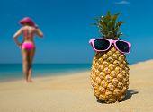 Cheerful pineapple glasses and a woman in a bikini sunbathing on the beach on sea background. Ideali
