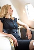 Attractive rich woman looking through window in private jet