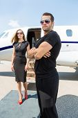 stock photo of bodyguard  - Bodyguard with arms crossed standing against elegant woman and private jet - JPG