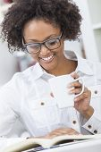 A beautiful happy mixed race African American girl or young woman wearing glasses drinking coffee or tea and reading a book in her kitchen at home
