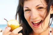 Woman Eats Fruit On The Beach