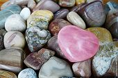 stock photo of rose-quartz  - rose quartz heart on multicolored background sea pebbles - JPG