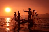 picture of canoe boat man  - Silhouette of traditional fisherman in wooden boat using a coop - JPG