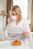 Pretty blonde in bathrobe drinking coffee and reading newspaper at home in the living room