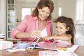 stock photo of granddaughters  - Senior woman scrapbooking with granddaughter - JPG