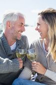 Couple enjoying white wine on picnic at the beach smiling at each other on a bright but cool day