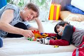 pic of babysitting  - Handsome father playing cars with disabled son on floor mat - JPG