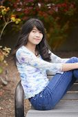 Young Preteen Girl Sitting On Park Bench Outdoors