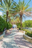 MIAMI, USA - MAY 20, 2014 : People enjoying the weather and walking along a seaside path in South Beach