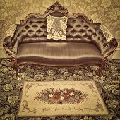 An antique sofa and hooked mat with a vintage sepia filter.