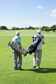 picture of golf bag  - Golfer friends walking and holding their golf bags on a sunny day at the golf course - JPG