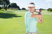 Lady golfer teeing off and smiling at camera on a sunny day at the golf course