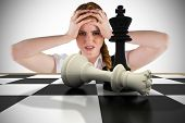 Stressed businesswoman with hands on head with chessboard against white background with vignette