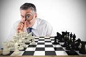 Composite image of focused businessman with magnifying glass with chessboard