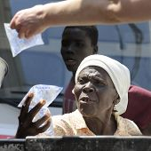 SAINT MARC, HAITI - FEBRUARY 22, 2013:  Close-up of an elderly Haitian woman accepting a bags of dri