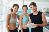 Fit women with trainer taking notes and smiling at camera at the gym