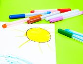 Color markers with child's drawing of the sun on a table