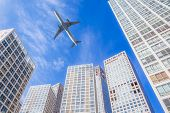 Airplane flying in business district sky,motion blur