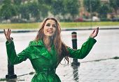 picture of rain  - Beautiful woman in bright green coat posing in the rain - JPG