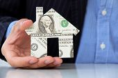 business man holding banknote house icon