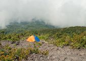 Tent On The Mountain In Fog And Clouds. Volcano Mount Merapi.