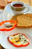 Egg (bullseye) in capsicum with brown bread and tea