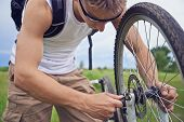 stock photo of bicycle gear  - Man cyclist checks brake wheel of bicycle in summer park repair of bicycle - JPG