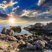 Calm Sea Wave On Rocky Shore At Sunset