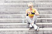 A picture of a rollerblader resting on concrete stairs and using a cellphone