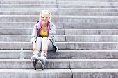Woman with roller blades sitting on concrete stairs