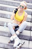 A picture of a rollerblader resting on concrete stairs and talking on cellphone
