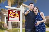 Young Happy Pregnant Hispanic Young Couple with House Keys in Front of Their New Home and Sold For S
