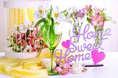 Freesias in glasses on table on fabric background