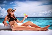 Sexy woman relaxing on luxury beach resort, sitting on lounger and drinking cocktail, summer vacatio
