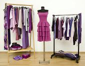 Wardrobe with purple clothes arranged on hangers and a dress on a mannequin.