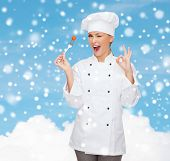 cooking, people, holidays and food concept - smiling female chef or cook with fork showing ok gesture over blue snowy sky and cloud background