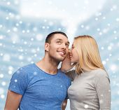 relationships, love, people, information and couple concept - smiling girlfriend telling boyfriend secret over snow and city buildings background