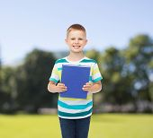 education, childhood and school concept - smiling little student boy with blue book over park background
