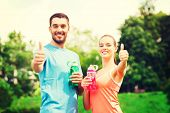fitness, sport, friendship and lifestyle concept - smiling couple with bottles of water showing thumbs up outdoors