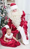 Little girl sits in Santa Nicolai's bag