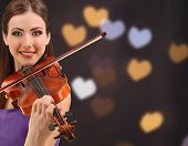 Beautiful young girl with violin on bright background